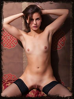 Newcomer Tirata poses on top of the sofa and showcasing her naked, delectable body in black fishnet stockings.