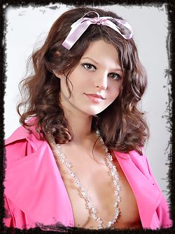 Adorably cute Niki A with perfectly curled brown hair that frames her pretty face, her naked body playing peek-a-boo in a bubblegum pink coat