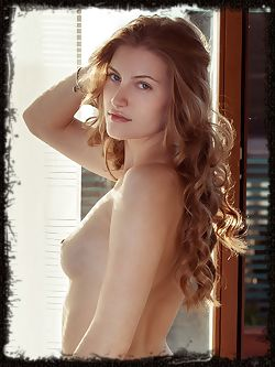 Blondie Bretona bares her plump pussy and slender body as she poses by the window.