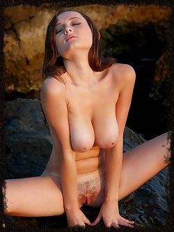 Amateur model with large breasts and nice bush goes outside and nude in the rocks by the sea.