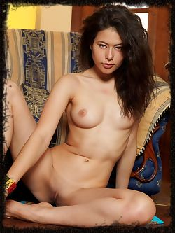 Jackie D and her hypnotizing look as she lounges naked by the sofa